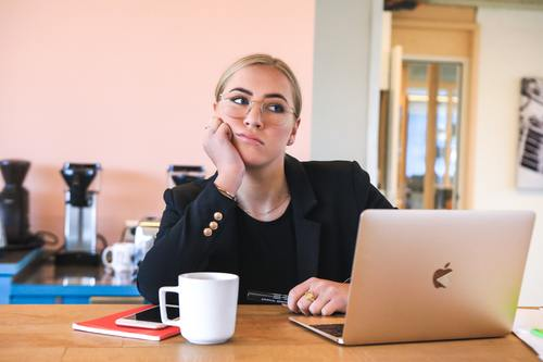 Woman looking fed up next to laptop