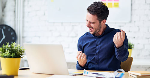 Young man celebrating in office while looking at laptop