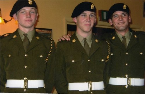 Photo of three men dressed in their armed forces uniform. Marc is central.