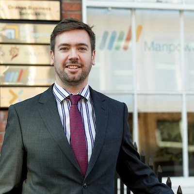 John Galvin's image.He is in a suit standing outside the Manpower Ireland office in Dublin, behind the front door with ManpowerGroup branded logos. Right Management, Experis and Manpower.