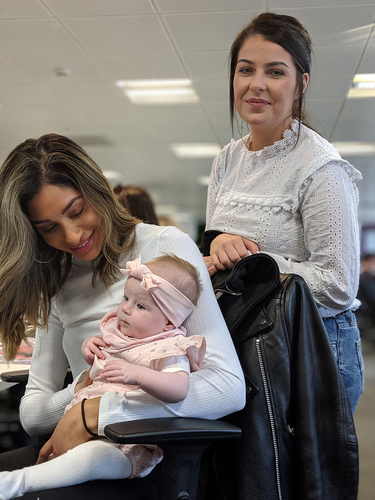 A brown haired woman holding a baby in a pink headband whilst in an office