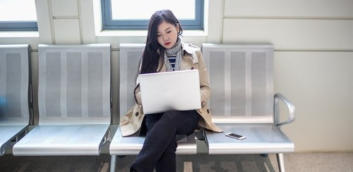 young asian woman on laptop in train station