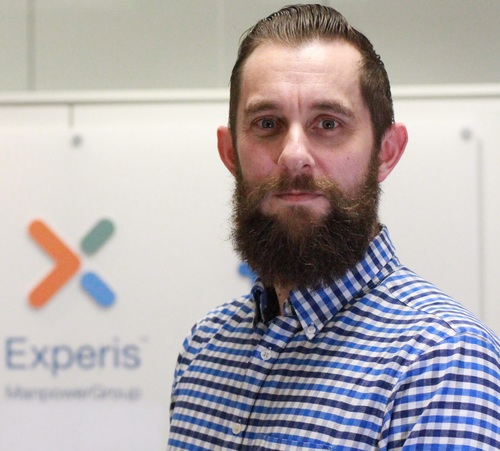 Jonny Edgar's image in the office with Experis branded logo on the wall behind him.