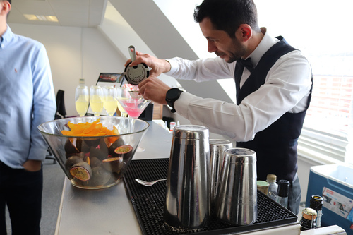 A barman pouring a pink cocktail