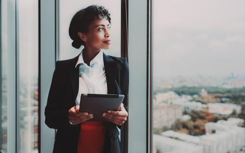Female boss looks out of boardroom window